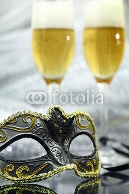 Vintage carnival mask in front of champagne glasses