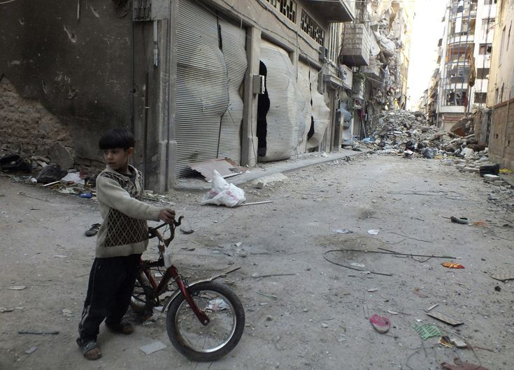 A boy holds a bicycle near debris and damaged buildings in Homs, on March 25, 2013.