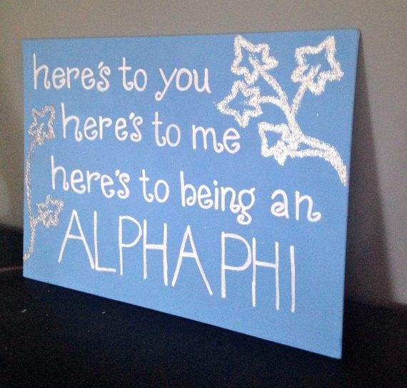 """This is a painted canvas with the quote, """"here's to you, here's to me, here's to being an Alpha Phi."""" This is great to give to a sister or for big little reveal. The color of the canvas can be changed. The size of the canvas is about 10inX12in."""