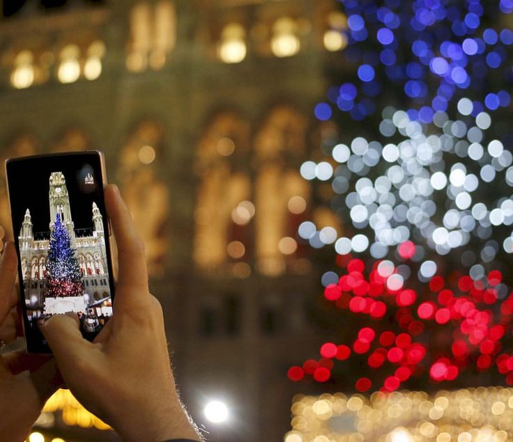 A tourist takes a picture of a #Christmas tree lit in the blue, white and red colors of #France's national flag in tribute to victims of last Friday's attacks in Paris, in front of the city hall building in #Vienna, Nov. 19, 2015. CREDIT: Leonhard Foeger/Reuters  SEE MORE at ABCNews.com #abcnews #ParisAttacks #Paris