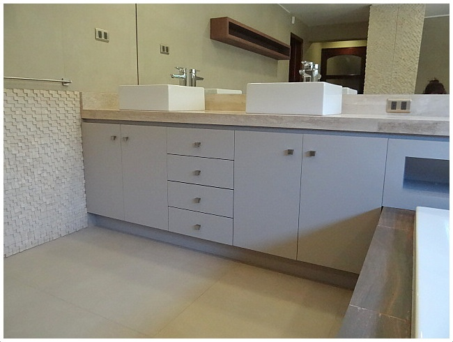 Mueble enchapado con puertas y cajones para guardado.  Cubierta de mármol.