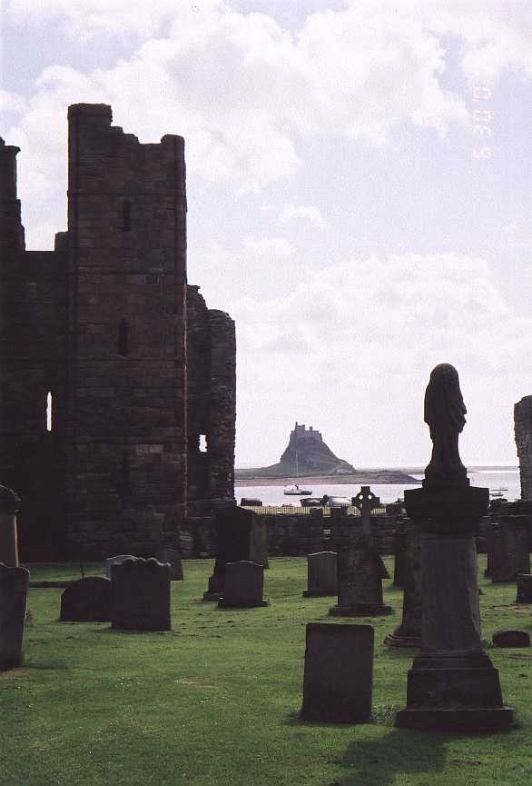 The ruins of the Benedictine priory  and the cemetery on LINDISFARNE..... (Lindisfarne castle on the island can be seen in the background)