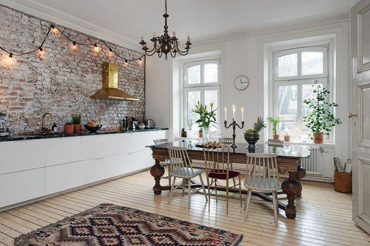 Klik hier en kom binnenkijken in deze super mooi eclectische woonkeuken met een bakstenen keuken achterwand, marmeren werkblad, gouden kraan en afzuigkap!