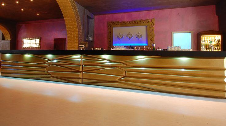 NARCISO, bancone ideale per un lounge bar serale. A prima vista ricorda molto un lingotto grazie al suo frontale color oro metallizzato ed il top con finitura marrone scuro opaco. La luce sotto al piano di servizio lo rende ancor più d'impatto per un pubblico esageratamente chic.