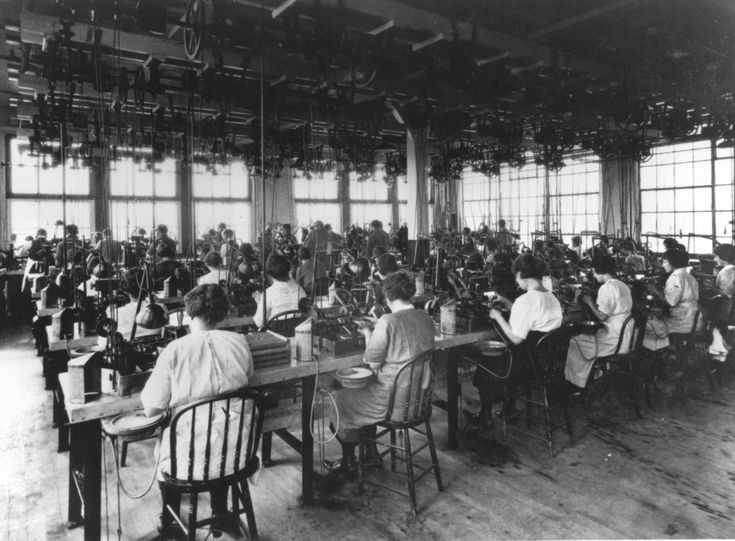 View of women factory workers seated at their work stations while operating machines to polish lenses, during the early twentieth century.