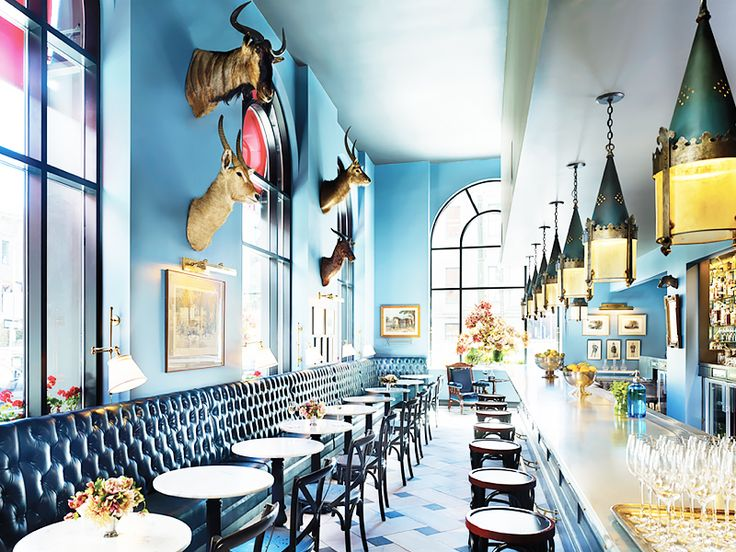 Blue dining space with tufted bench and antique lighting