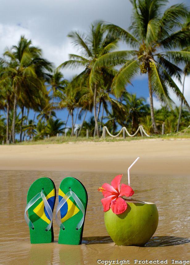 Chinelo com a bandeira do Brasil ao lado de coco verde numa praia tropical da Bahia. Praia do Cassange, Península de Maraú, Bahia...