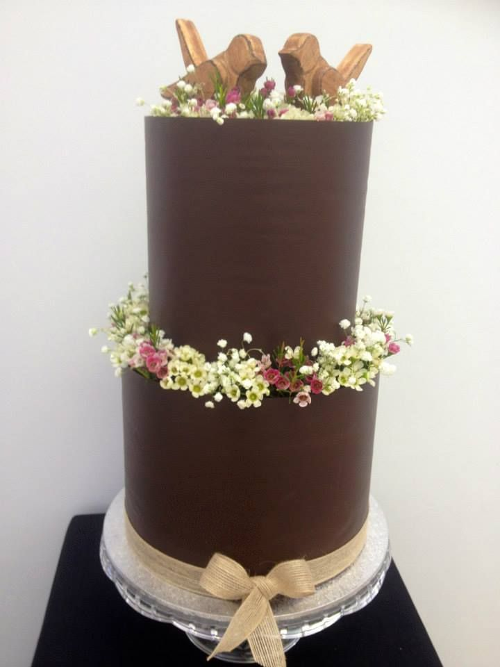 A taller chocolate collared cake with hessian ribbon and two sweet birds