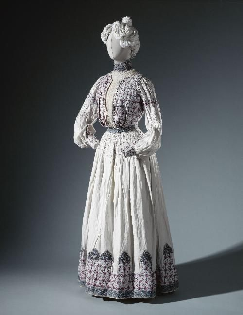 Summer dress consisting of a blouse and skirt, by Jacques Doucet, 1904, at the Palais Galliera. White cotton, panels of red and blue cross-stitch embroidery.