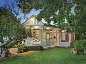 Weatherboard edwardian house exterior with balcony & hedging -
