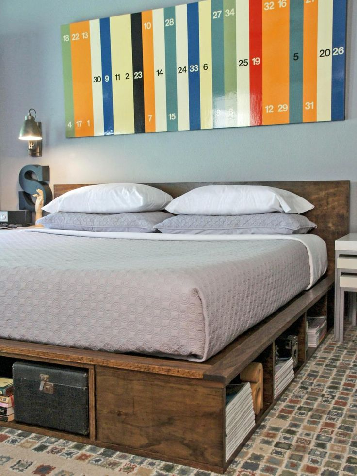 This eclectic bedroom features a rustic wood platform bed with soft gray bedding. A piece of fun, colorful artwork hangs above the bed, adding vibrant color to the space.