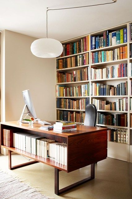 In this study designed by Maria Speake of Retrouvius, the owner's sizeable collection of books spreads from the wall of architectural shelving to the wonderful Danish Rosewood desk from Paere Dansk.