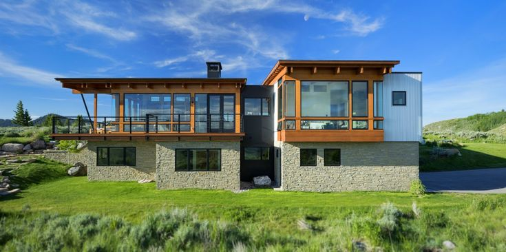 The leeward side of the house takes in the commanding views Tagged: Exterior, House, Wood Siding Material, Glass Siding Material, Stone Siding Material, Metal Siding Material, and Shed RoofLine. Skyview by Design Associates Architects - Photo 4 of 21