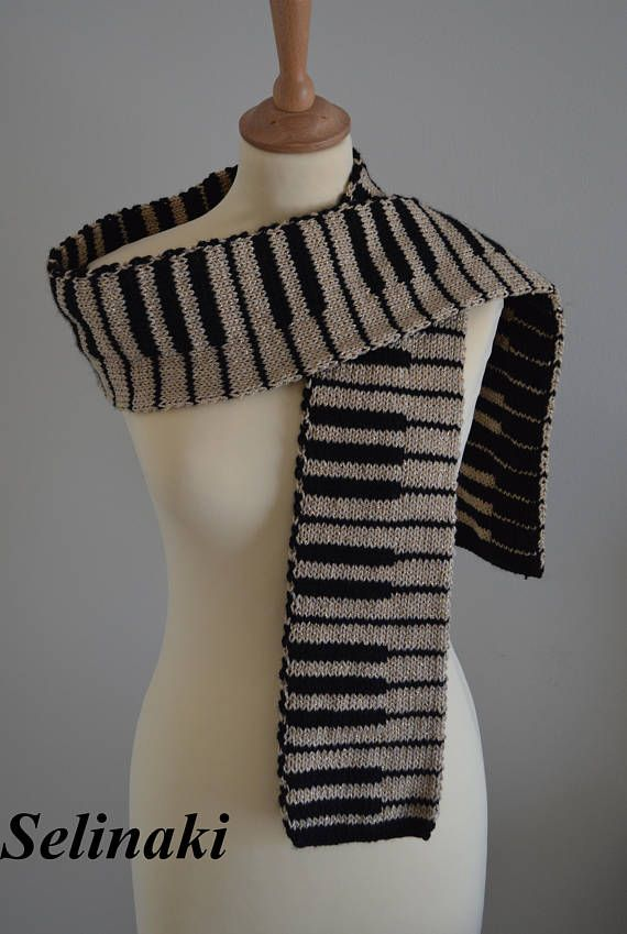 Hand-knit golden glitter piano keyboard scarf.  The scarf is double sided (one side is gold color, the other side is black), handmade by me with 100% acrylic yarns.  Approximately 176 cm long x 14 cm wide (69 inches long x 5.5 inches wide)  Ready to ship.  For the matching gloves please visit https://www.etsy.com/listing/513840946/knit-golden-piano-fingerless-gloves-gold  For the matching hat please visit https://www.etsy.com/listing/516821544&#x2F...