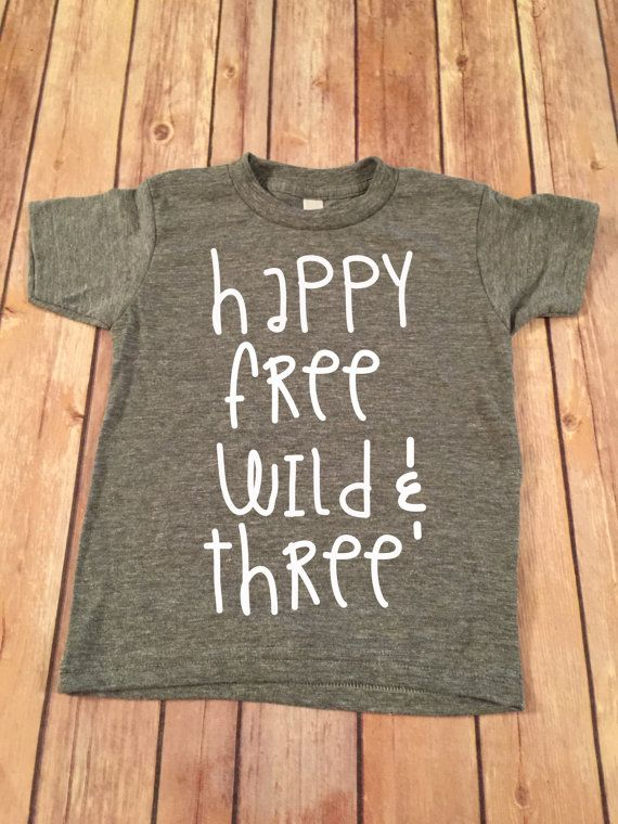 This is a super cute Happy Free Wild and Three on a heather gray short sleeve shirt. The shirts are made of: Jersey 30/1, 100% cotton ring spun combed.
