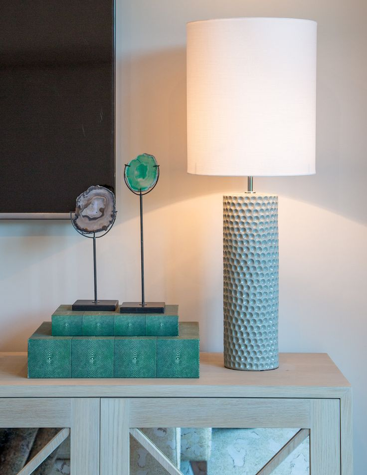 Serene and soothing, the teal colour scheme in our Surrey barn design is highlighted in this unique ornament and lamp, resting beautifully upon the rustic wooden cabinet.