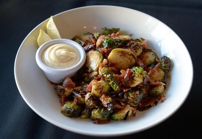 Fried Brussels sprouts with lemon aioli and applewood smoked bacon is prepared by Executive Chef  Darius Somary at the Hotel Sutter Restaurant in Sutter Creek, Calif., on Thursday, Aug. 21, 2014. Somary studied culinary arts in San Francisco, worked at Oliveto in Rockridge and then founded SpringLoaf Catering in Lafayette before relocating to Sutter Creek with his family. (Susan Tripp Pollard/Bay Area News Group)