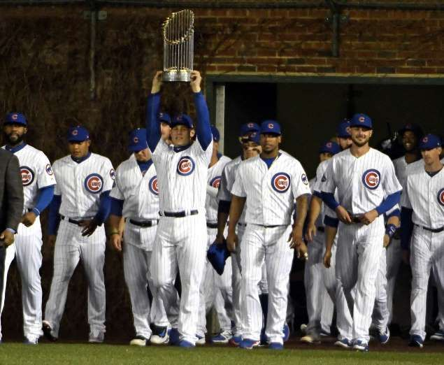 LONG TIME COMING:    Chicago Cubs first baseman Anthony Rizzo carries the World Series trophy before the home opener against the Los Angeles Dodgers on April 10 in Chicago. The Cubs won the World Series for the first time since 1908.
