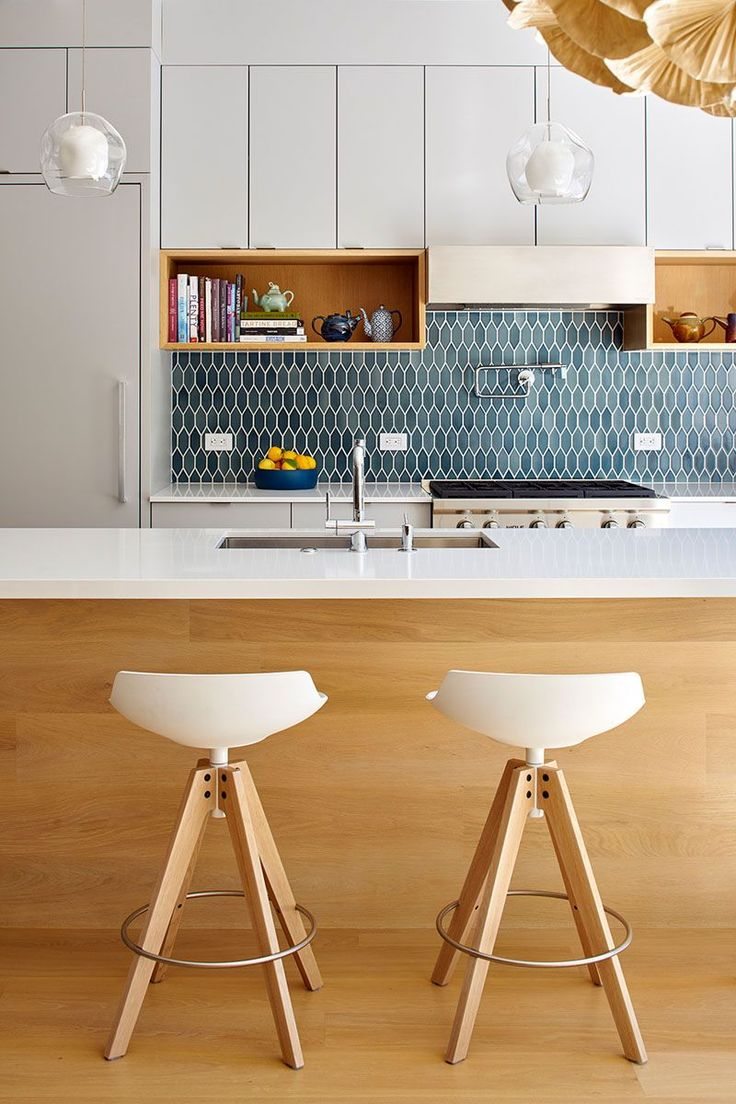 Blue tiles add some color to the white and wood kitchen palette.
