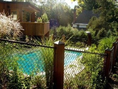 Customized wood post housings combined with black chain link fence enhance the natural beauty of a back yard landscape
