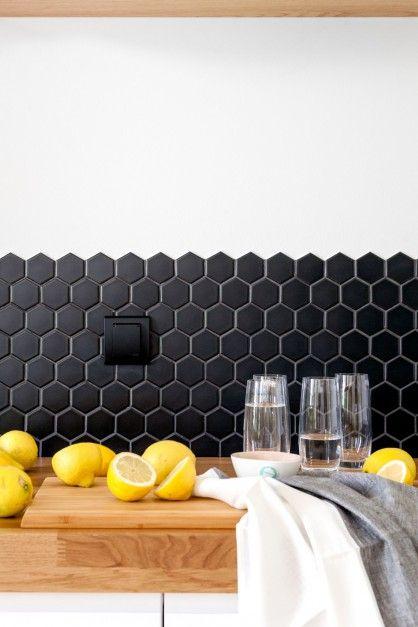 Ścianę nad blatem wykończono modnymi płytkami heksagonami, czyli mozaiką ciętą w romby w czarnym kolorze. Czarne są również inne elementy wykończenia kuchni takie jak zlew, bateria czy kontakty. Projekt: Olga Nowosad. Fot. Black Oak Studio.