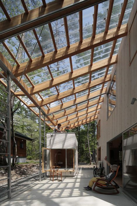 Cedar-clad villa by Naka Studio shelters a huge terrace beneath its roof.