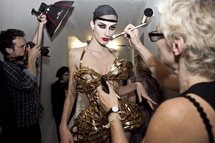 Collection Haute Couture automne-hiver 2012-13  Model Thana Kuhnen backstage.  Modèle n°57  Dévoreuse : Corset cage à basques, baleiné et lacé de cuir or, hanches et seins projetées.   www.jeanpaulgaultier.com #JPGaultier #PFW #couture #backstage #corset #cage