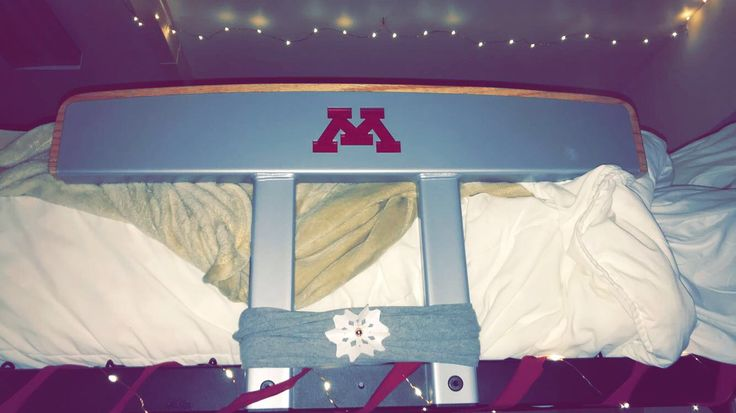 Christmas dorm decor on a student budget! Grey cut up tee shirt, college ruled paper snowflake, gold push pin, maroon tee shirt cut in strips and wrapped around bed, and Christmas lights