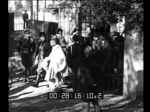 Giornale Luce B0027 del 18/12/1931 Descrizione sequenze:treno in stazione con dentro Gandhi, folla vicino al treno ; Gandhi saluta dal finestrino affiancato ...