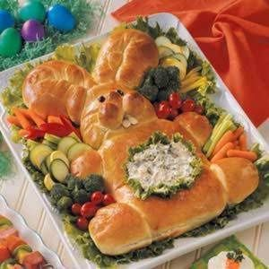 Easter Bunny Bread - 2 loaves (1 pound each) frozen bread dough, thawed; 2 raisins; 2 sliced almonds; 1 egg, lightly beaten; Lettuce leaves; Dip of your choice