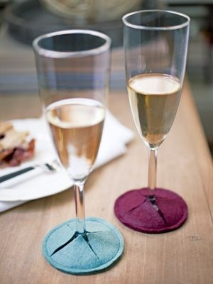 Not only do these accessories protect tabletops; when fashioned in a variety of hues, they also help guests keep track of their champagne glasses. Measure the diameter of a glass's base, then cut two slightly larger felt circles. Cut an X across the middle of one circle before stitching the piece atop the other.
