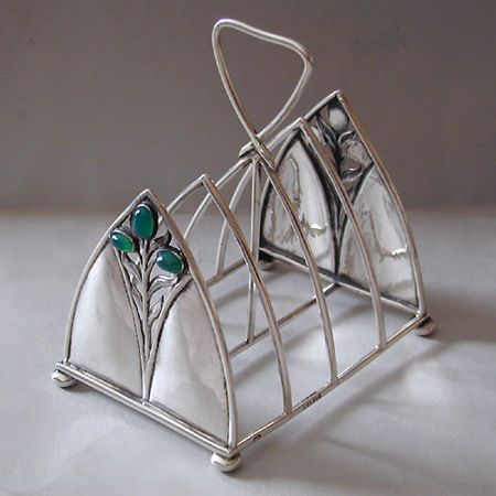 C. R. ASHBEE  -  THE GUILD OF HANDICRAFT Ltd. (1888-1907)   An Arts & Crafts silver toast rack set with green chalcedony.