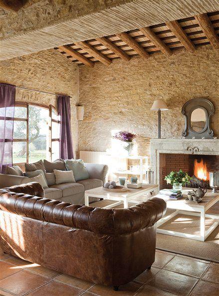 Salón rústico con chimenea y sofá chester
