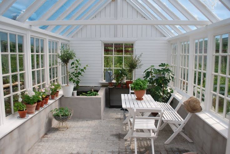 greenhouse/sunroom- Beautiful white greenhouses with lush green plants, leaves and leafy florals   Dream garden   Gardening inspiration   Greenhouse and conservatory ideas   By jewellery label AU REVOIR LES FILLES   Shop beautiful stacking rings and fine necklaces at www.aurevoirlesfilles.com