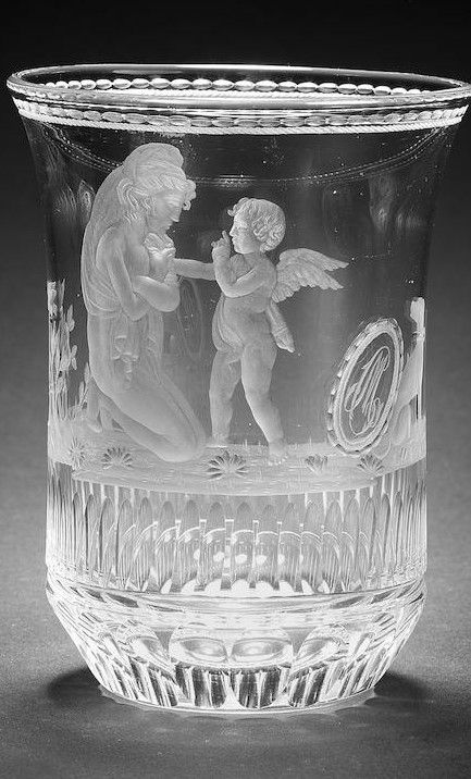 A fine Bohemian engraved beaker attributed to Hieronymus Hackel, circa 1820 The slightly waisted cylindrical form with everted rim, decorated with a figure of Venus kneeling before a winged Cupid, a pair of lovebirds atop a short column and a thorny rose bush, with a dog seated next to a shield inscribed with the initials CM, all above a band of flutes, the chamfered base cut with facets, the rim with a formal border of circlets, 12.3cm high