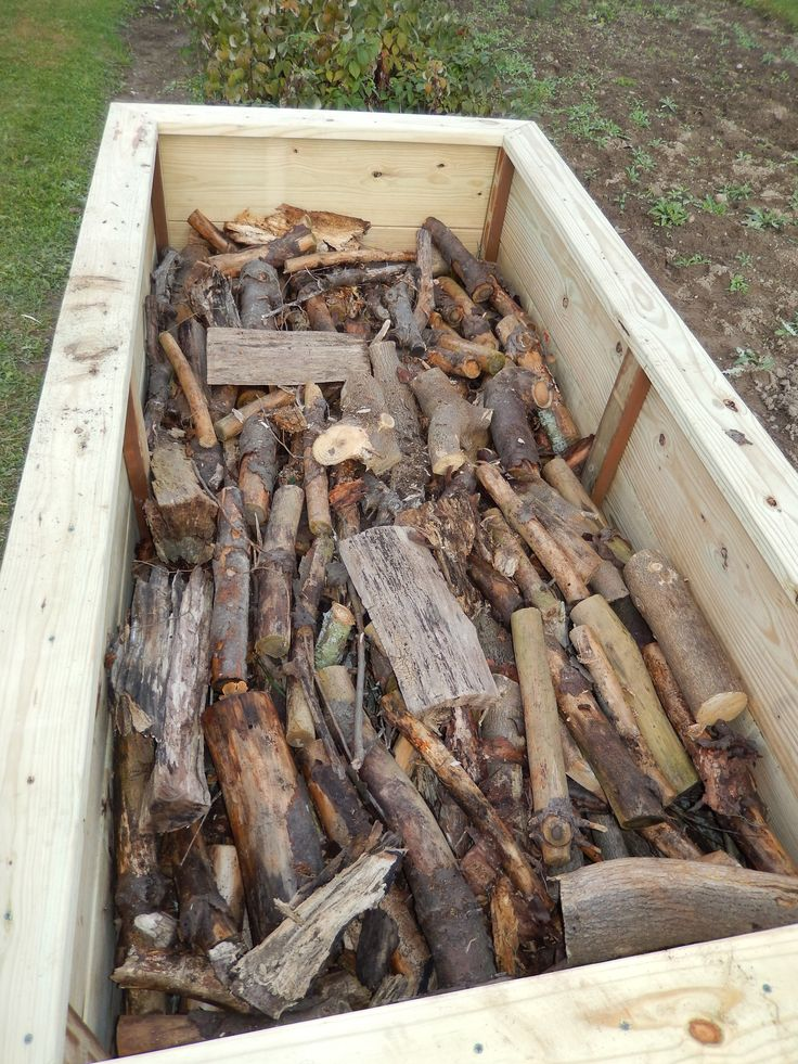 Step #2 of Hugelkulture raised bed... filling approx half full with already rotting and newly cut wood, sticks, branches.