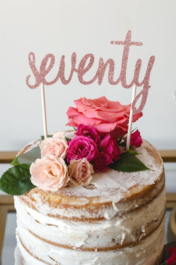 Whimsical 70th birthday party cake topped with fresh flowers