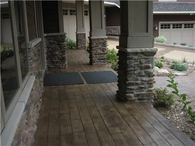 Stamped concrete that looks like hardwood flooring (so cool) and I love the pillars with the stone. All outdoor patio and porch for the new house.