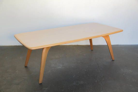 Refinished blonde wood surfboard coffee table stamped by Heywood Wakefield. Constructed in solid birch with curved tapered legs and a rounded rectangular top that tapers slightly. Great condition, very minor discoloration in some areas from previous use - excellent vintage condition.