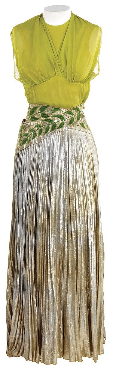 """Broadway Melody of 1940 dance dress designed by Adrian. (MGM, 1940) Lime green chiffon, sleeveless bodice with silver lame pleated skirt decorated at waist with green velvet leaves. Hook & eye with zip back closure. Top has MGM studio cleaning tag. Skirt has handwritten, """"M. Davis"""" along waistline."""