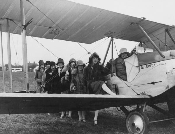Female flying enthusiasts queuing up for ride in an aeroplane at air show.  Location:	Hadleigh, United Kingdom  Date taken: 1927