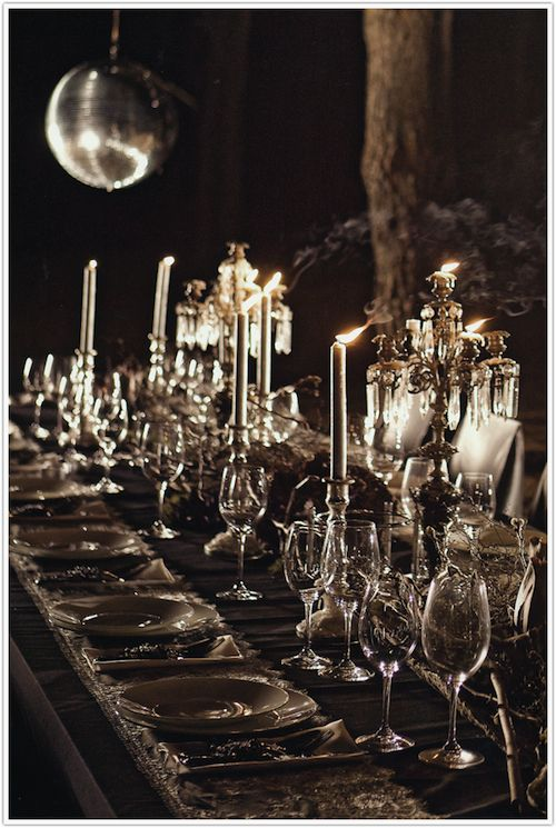 Halloween masquerade table - beautiful dark ambiance with candles, clear glassware, and dishes.