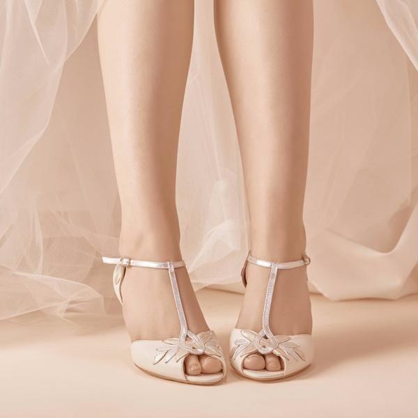 Brautschuhe mit niedrigem Absatz und Blumen-Ornamenten in Gold und Silber. Mit seinem Absatz von 6cm ist der Islasehr elegant und hat dennoch hohen Tragekomfort. Das T-Riemchen am Spann und klassischem Schnallenverschluss verleiht dem Brautschuh eine Sandalen Optik. Der Schuh Isla besticht durch ein zeitloses, schlichtes Design, das sich stilsicher mit einer Vielzahl Braut-Outfits kombinieren lässt. Die Brautschuhe werden aus hochwertigem Leder von hochqualifizierten Handwerkern in Spanien…