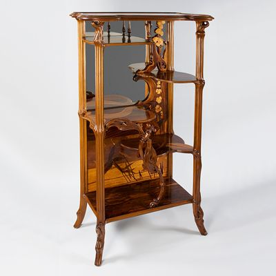 "A French Art Nouveau walnut ""Etagere aux Libellules."" Both the inlay and the structural elements of this Etagere are derived from plant forms. The elaborate inlay depicts a landscape of reeds and orchids while the legs and shelves are suggestive of branches and pond lilies. A large dragonfly, connecting the middle and lower shelves dominates the piece"