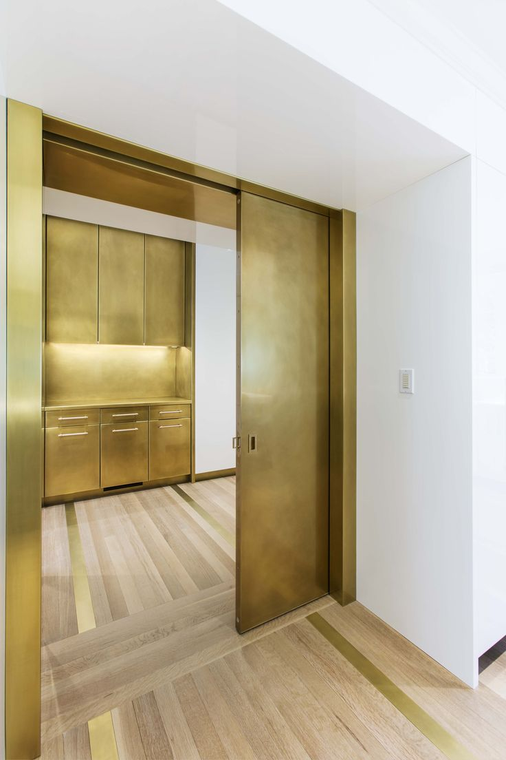 Retractable brass doors reveal custom brass pantry. A dream kitchen indeed!