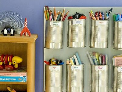 Hot glue heavy-duty magnets to ten soup cans and stick them to a steel cookie sheet. Hang it within kids' reach using a plate hanger. Use the cups to hold crayons, chalk, markers and even Legos. Label the cans for easy clean up.""