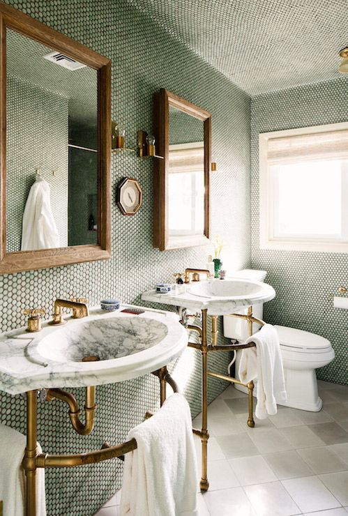 Fabulous bathroom features ceiling and walls clad in green penny tiles accented with dark grout lined side by side 2-leg brass washstands with curved marble sinks fitted with brass faucets under wood beveled mirrors illuminated by brass sconces.
