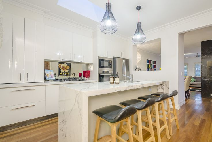 The renovated kitchen with Calacutta Marble and the overhang of gorgeous lights, ample storage and Miele appliances ties the stylish look together. 18 West Court, Williamstown.