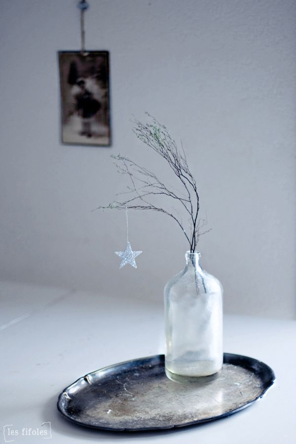 Understated sparkle: A simple branch and ornament on a weathered platter--the perfect little holiday tablescape. Via Les Fifoles.