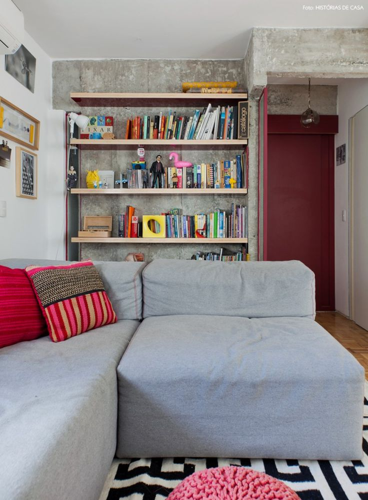 Sala de estar com parede de concreto, estante de madeira revestida com fórmica e porta pintada de vinho.